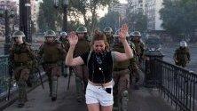 Протестите в Чили не стихват - демонстрантка плаче, ескортирана от полицаи по време на протест в Сантяго.