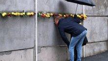 Двойка гледа през дупка в мемориал в Берлин по повод 30-тата годишнина от падането на Берлинската стена.