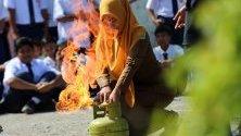 Индонезийска учителка взима участие в учение за гасене на пожар в училище в Банда Ачех.