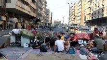 Иракски протестиращи си почиват зад барикада по време на демонстрация в Багдад срещу правителството.