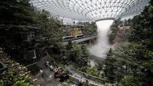 """Пътници разглеждат 40-метровия Дъждовния вортекс на летище """"Чанги"""" в Сингапур - най-големият в света водопад в затворено помещение. Построена за над 1 мил. евро, 10-етажната структура свързва терминалите на летището. В нея има хотел, магазини и ресторанти."""