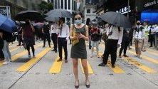 Демонстранти и служители са блокирали път по време на обедна почивка с флашмоб в центъра на Хонконг. В града протестите продължават шести месец.