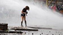 Полицията облива с водни струи демонстрантка по време на поредния ден на протести в Сантяго, Чили.