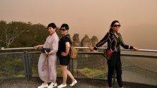 Туристи позират пред скалния феномен Трите сестри в Катумба край Сидни, Австралия. Горските пожари са пред мегаполиса.