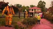 Къщи, покрити с химическо вещество, възпиращо огъня и хвърлено от хеликоптер, Южен Турамура край Сидни, Австралия. Най-малко 60 пожара горят в Нов Южен