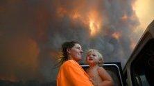 Майка с дъщеря се евакуират от горските пожари край Нана Глен, Нов Южен Уелс, Австралия- Над 50 пожара горят в региона, като близо половината не са овладяни.