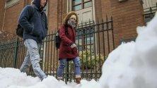Хора в дебели дрехи в университетски кампус в Чикаго, Илинойс, САЩ. Регионът е обхванат от арктически студ.