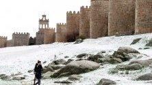 Жена минава край градските стени на Авила след снеговалеж, Централна Испания. Ниско налягане преминава над страната със снеговалежи, дъждове, ветрове и спадане на градусите.