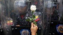 Протестиращ подава бяла роза на спецчастите по време на студентски протест пред Университета на Венецуела в Каракас.