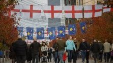 Пешеходци минават под английски и косовски знамена, окачени за мача от Евро 2020 между Косово и Англия в Прищина.