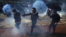 Протестиращи с чадъри срещу полицейските сили, изстрелващи сълзотворен газ, по време на демонстрация в Хонконгския политехнически университет.