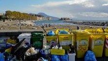 Хора почистват пластмасови боклуци и отломки след бурите, донесени от вълните на брега край Неапол.