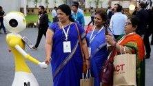 Индийки се ръкуват с робот по време на 22-рото технологично изложение в Бангалор, Индия.