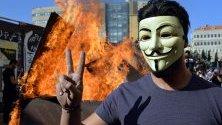 Протестиращ с маска показва знака на победата пред клада, запалена от демонстранти, блокирали път към парламента в Бейрут, Ливан. Сесията на парламента е отложена неопределено заради натиска от улицата.