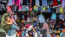 Индонезийки сортират дрехи на пазар за стоки втора ръка в Медан, Индонезия. Централната банка обяви, че се очаква инфлацията в страната да е около 3,1%.