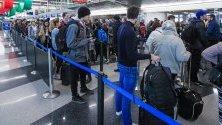 """Чакащи пътници на летище """"О`Хеър"""" в Чикаго, САЩ, завръщащи се по домовете си за Деня на благодарността. Тази година пътниците срещат трудности заради зимните бури и силните ветрове."""