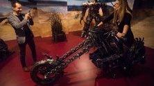 Посетители позират върху метална скулптура на мотор, направена от авточасти втора ръка, по време на изложба в Будапеща, Унгария.