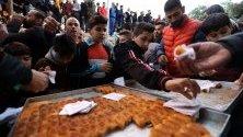 Палестинци се черпят с безплатна баклава преди сутрешната молитва в джамията Ибрахими или гробницатана патриарха в Хеброн.