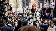 Патрик Матурин облечен като De Nieuwe Sint (Новият Свети Николас) пристига на кон в центъра на Амстердам. Алтернативният светец раздава рози, бонбони и плодове и участва в музикално парти.