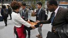 Участници в срещата за измененията на климата в Мадрид COP25 се черпят с чурос при пристигането си.