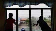 Филипинци гледат през прозорец на евакуационен център силните ветрове, докарани от тайфуна Камури.