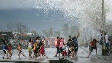 Деца си играят на силните вълни при дига в град Легазпи, Филипините, предизвикани от тайфуна Камури.