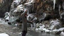 Човек се опитва да запази равновесие край замръзнал поток след рязко спадане на градусите в Кашмир, Индия.