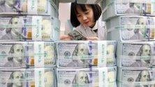 Служителка брои стодоларови банкноти в централата на банка KEB Hana в Сеул, Южна Корея. Резервите от чуждестранна валута в страната достигнаха рекорд от над 407 милиарда долара.
