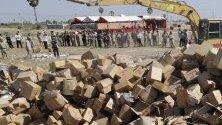 Камбоджанските власти унищожават конфискувани фалшиви продукти в предградията на Пном Пен.