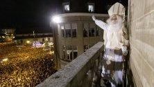 Мъж, преоблечен като Свети Николас, поздравява събралите се хора от централната катедрала във Фрибург, Швейцария. Светецът е патрон на града - с падането на нощта той язди магаре по улиците му, начело на процесия пред катедралата, откъдето изнася реч.