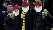 Футболни фенове с бради на Дядо Коледа по време на мач от германската Бундеслига.