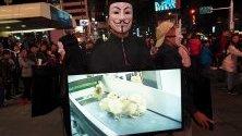 """Членове на """"Анонимните за Безгласните"""" показват видеокадри на животни, убивани в кланици, по време на протест в Тайпе, Тайван."""