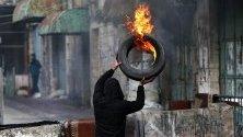 Палестинец подготвя горяща барикада по време на сблъсъци с израелските части в Хеброн, Западен бряг. Палестинците протестират срещу плана на Израел да разруши пазар за плодове и зеленчуци в стария град, за да изгражда нов кибуц.