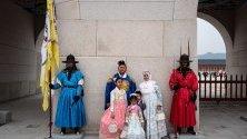 Туристи, облечени в традиционно южнокорейско облекло ханбок, позират за снимка по време на посещение в двореца Кьонбокун в Сеул.