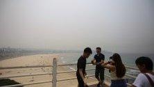 Хора на прочутия плаж Бонди Бийч в Сидни на фона на стелещия се дим над града от горските пожари.