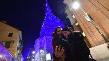 Туристи се снимат край монумента Моле Антонелиана в Торино, Италия, осветен със светлини за Коледа.