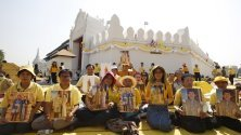 Тайландци държат снимки на крал Маха Вачиралонгкорн и кралица Сутида докато се състои церемонията в чест на една година от коронясването му в двореца в Банкок.