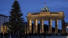 Осветената Бранденбургска врата в Берлин с коледна елха пред нея.