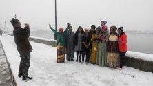 Туристи позират пред езерото Дал по време на снеговалеж в Шринагар, Индийски Кашмир. Полетите от местното летище са възпрепятствани за осми пореде ден - най-дългия период от 28 години.
