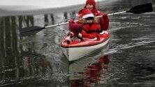 Дете и майка му, облечени като Дядо Коледа, участват в надпревара с каяци Santa Run в Минск, Беларус.