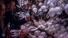 Хора разглеждат коледни топки на коледен базар в Ратхаусплац във Виена, Австрия.