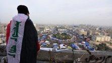 """Демонстратор се е качил на покрива на изоставена сграда близо до площад """"Ал Тахрир"""" в Багдад, Ирак, откъдето наблюдава палатков лагер на протестиращи."""