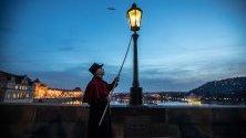 Дежурен пали лампите по Карловия мост в Прага, облечен в историческа униформа. Паленето е туристическа атракция по време на коледните праници.