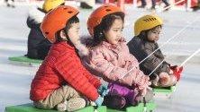 Деца се пързалят на шейни в градски парк в град Бусан, Южна Корея.