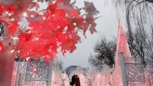 Разхождащи се московчани край декорация за празниците.