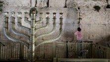 Момче поставя листче с желание в Стената на плача в Ерусалим, застанало до огромна златна Менора за еврейския празник Ханука.