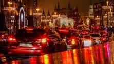 """Автомобили минават по улица """"Тверская"""" в Москва, украсена празнично за Нова година и Коледа."""