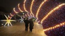 """Разхождащи се по украсен за Коледа мост пред катедралата """"Христос Спасител"""" в Москва."""