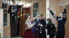 Ученици подготвят украса на новогодишна елха във физкултурен салон за празненство на Нова година в град Солигалич, Костромски регион, Русия.