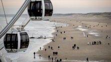 Разхождащи се семейства по плажа в Шевининген, Холандия, по време на почивните дни.
